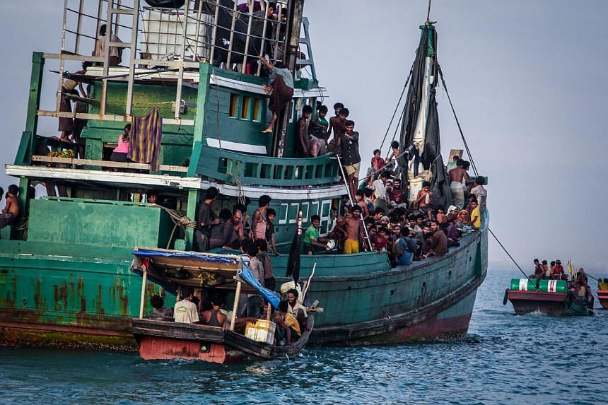 This photograph taken on May 20, 2015 shows Rohingya migrants resting on a boat off the coast near Kuala Simpang Tiga in Indonesia's East Aceh district of Aceh province before being rescued. Australian authorities work within the law to stop asylum s