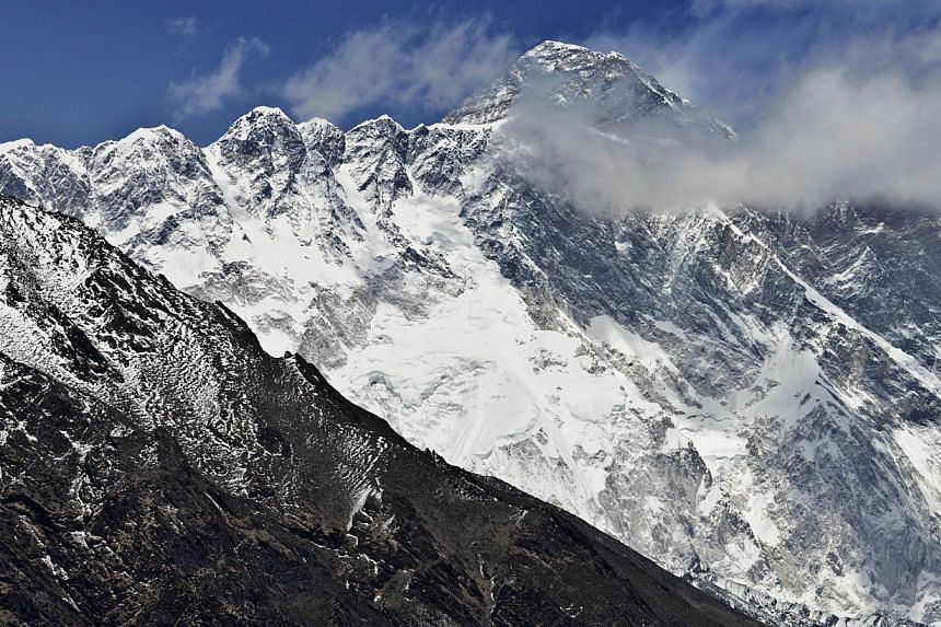 This photograph taken on April 20, 2015, shows a view of Mount Everest (centre, top) towering over the Nupse-Lohtse massif (foreground) from the village of Tembuche in the Khumbu region of northeastern Nepal. Mount Everest, moved three centimetres to