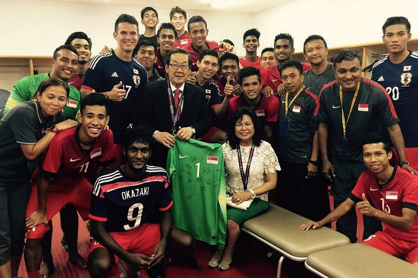Singapore's Ambassador to Japan Chin Siat Yoon (holding goalkeeper Izwan Mahbud's jersey) and his wife Wang Lee Moi (seated)  with the Lions in their dressing room after the 0-0 World Cup qualifying draw with Japan. -- PHOTO: COURTESY OF CHIN SI