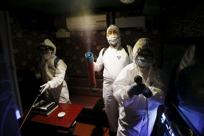 Workers disinfecting a karaoke establishment in Seoul, South Korea on June 16, 2015. Two South Korean hospitals are conducting experimental treatment on MERS patients, injecting them with blood plasma from recovering patients. -- PHOTO: REUTERS