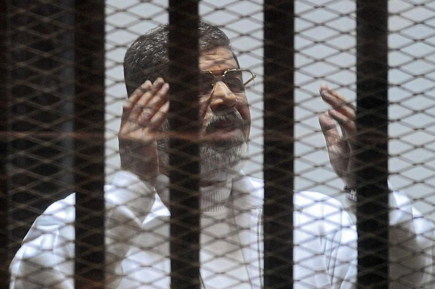 Former Egyptian president Mohamed Mursi gesturing in a cage in the courtroom where he stands charged of spying with Qatar, in Cairo, Egypt, on Feb 15, 2015. An Egyptian court sentenced Mursi to death on Tuesday, June 16, in a case related to a 2011 m