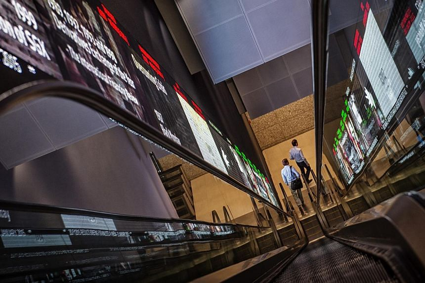 Pedestrians exit an escalator that runs past an electronic screen and ticker board that indicates stock figures at the Singapore Exchange (SGX) headquarters in Singapore, on Jan 21, 2015. -- PHOTO: BLOOMBERG