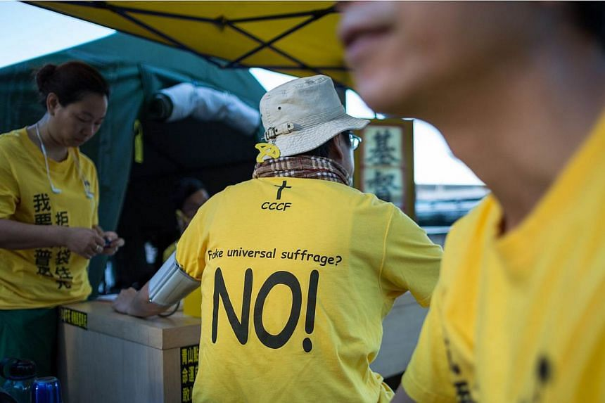 """A protester wears a t-shirt against """"fake universal suffrage"""" in a makeshift tent outside the Legislative Council in Hong Kong, China, on June 15, 2015. Hong Kong's Legislative Council (LegCo) will this week debate and vote on a bill on electoral ref"""
