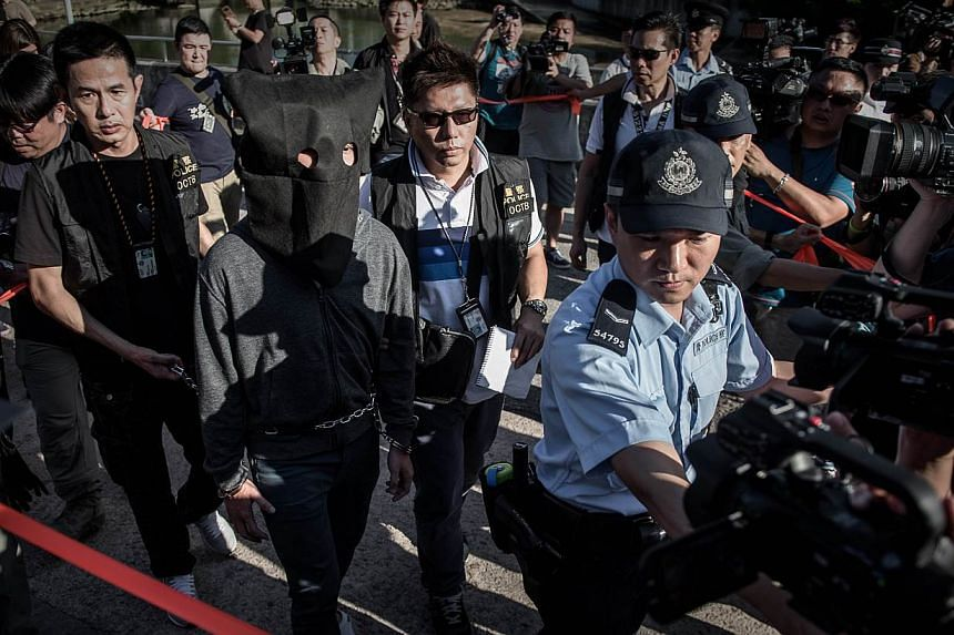 A suspect is escorted by policemen during a crime reconstruction in the east-coast district of Sai Kung in Hong Kong on June 16, 2015 a day after suspected explosives were seized at an abandoned television studio. China on Tuesday warned against
