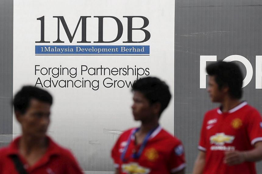 Men walk past a 1 Malaysia Development Berhad (1MDB) billboard at the funds flagship Tun Razak Exchange development in Kuala Lumpur in this March 1, 2015 file photo. -- PHOTO: REUTERS