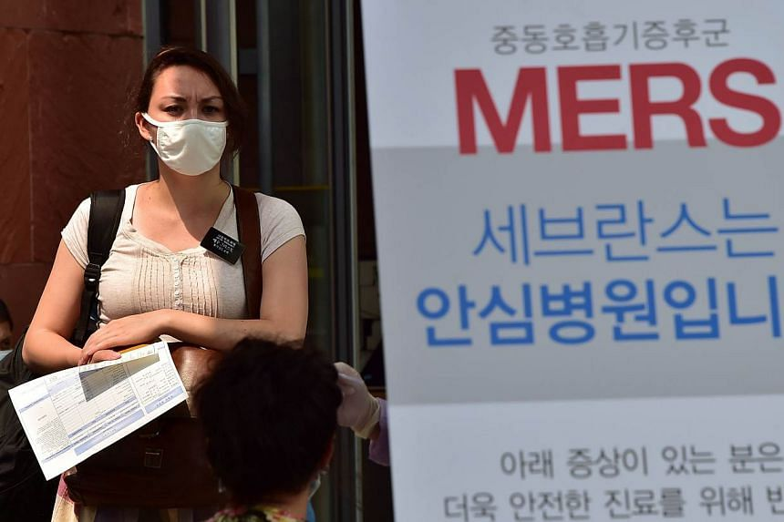 A woman wearing a face mask stands at a special clinic where patients with respiratory issues can be treated in an isolated space to prevent possible spread to other patients, at Severance Hospital in Seoul on June 16, 2015. A 65-year-old German