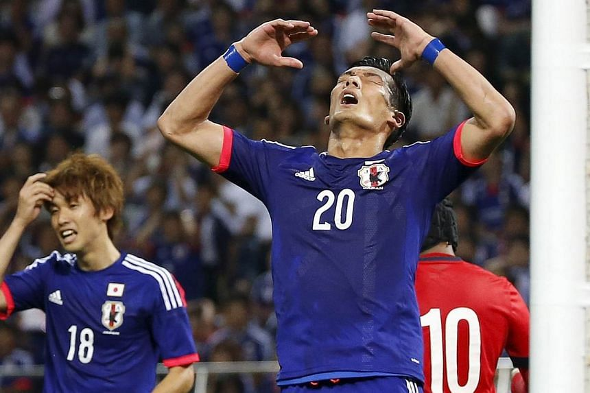 Japan's Tomoaki Makino (centre) with teammate Yuya Osako after missing a shot against Singapore. -- PHOTO: REUTERS