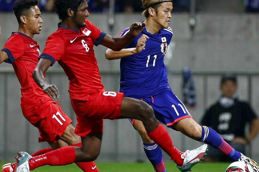 Japan's Takashi Usami fighting for the ball with Singapore's Madhu Mohana (centre) and Nazrul Nazari. -- PHOTO: REUTERS