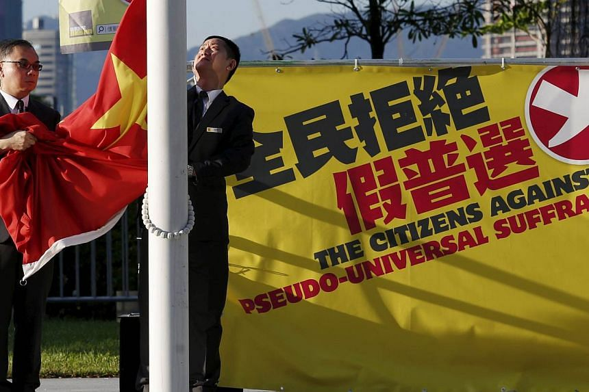 Flagbearers lower a Chinese national flag beside a banner set up by pro-democracy protesters outside Legislative Council in Hong Kong, China on June 16, 2015. -- PHOTO: REUTERS