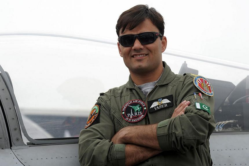 Pakistan Air Force Squadron Leader Yaser Mudasser poses in front Pakistan's JF 17 Thunder cockpit on the tarmac of the International Paris Airshow at Le Bourget on Monday. -- PHOTO: AFP