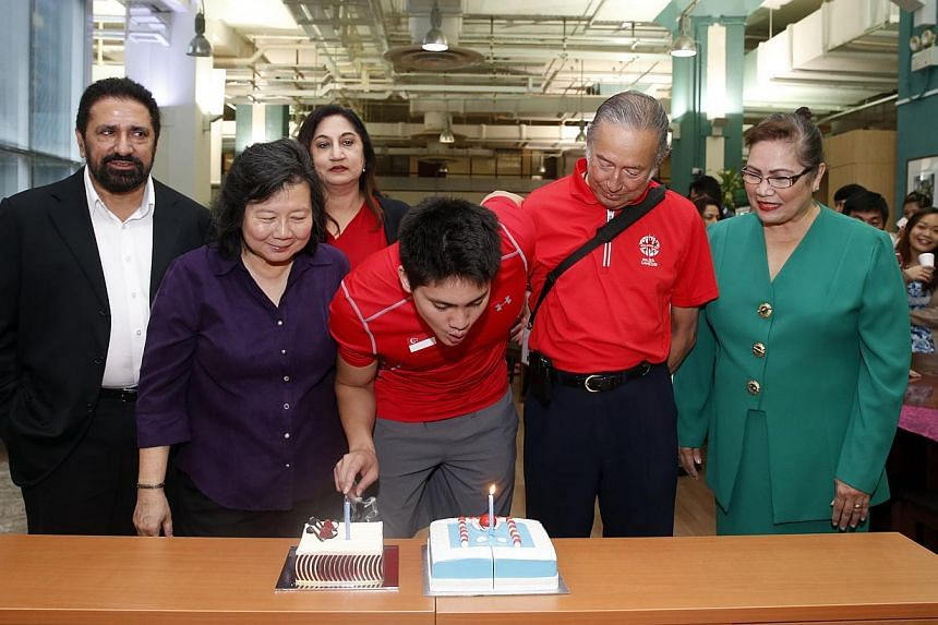 Joseph Schooling gets a birthday surprise in the news room with cakes from The Straits Times and the Eurasian Association. -- ST PHOTO: KEVIN LIM