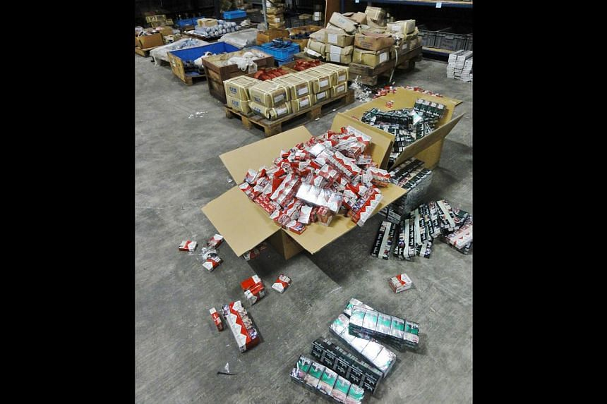 The duty-unpaid cigarettes were retrieved from the modified bed headboards and packed into boxes in the warehouse at Loyang Crescent. -- PHOTO: SINGAPORE CUSTOMS