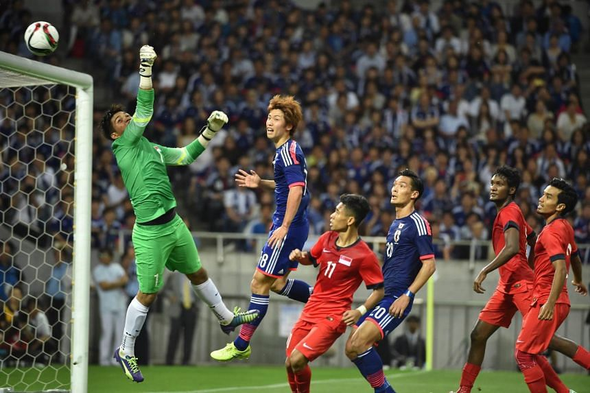 Singapore goalkeeper Izwan Mahbud punching a header from Japan's Yuya Osako (No. 18) above the bar in Saitama in front of a crowd of 57,533.