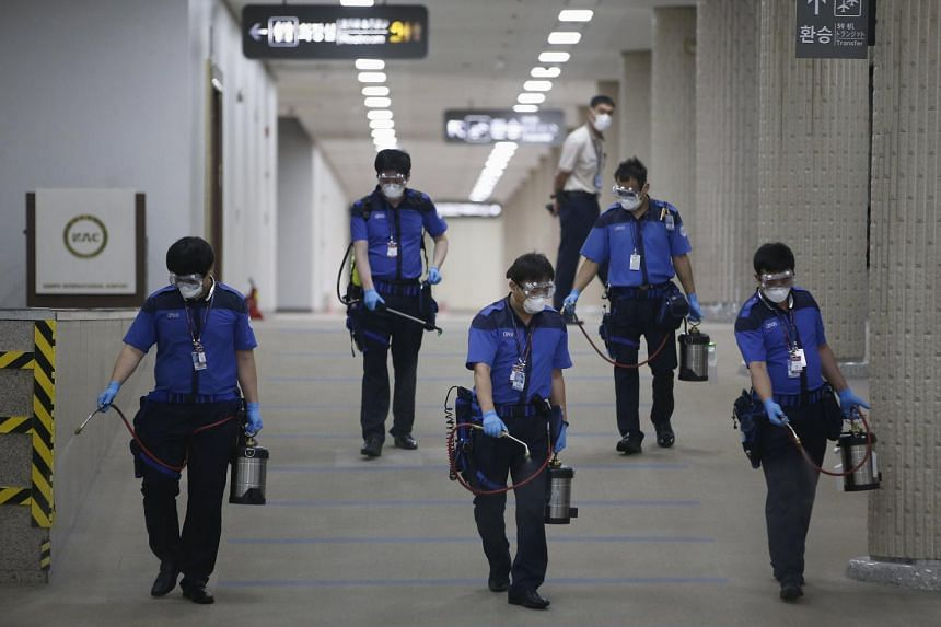 Employees from a disinfection service company sanitising Gimpo International Airport in Seoul.
