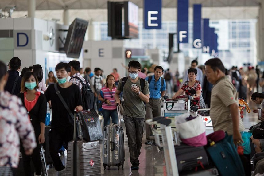 Masked travellers in the departure hall of Hong Kong International Airport last week as the city's authorities issued an outbound travel alert against visiting South Korea after the outbreak of Mers in the country.