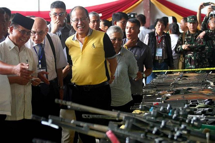MILF chairman Murad Ebrahim (wearing songkok) and Philippine President Benigno Aquino (in yellow) inspecting rebel firearms to be decommissioned during a ceremony in Mindanao on Tuesday.