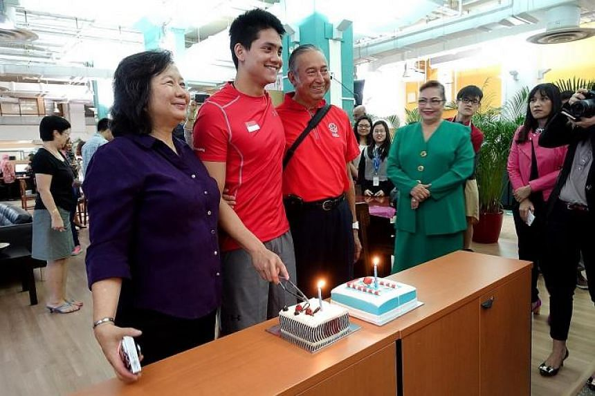 (Right) Joseph Schooling, seen here with his parents May and Colin Schooling, getting a birthday surprise in the ST newsroom with cakes from ST and the Eurasian Association yesterday, as the association's second vice-president Yvonne Pereira (in gree