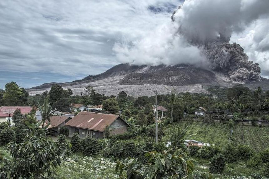 Mount Sinabung spewing ash, as seen from the nearest village in Karo district, North Sumatra province, yesterday. The volcano rumbled back to life in 2013, after a period of inactivity, and erupted violently over the weekend.