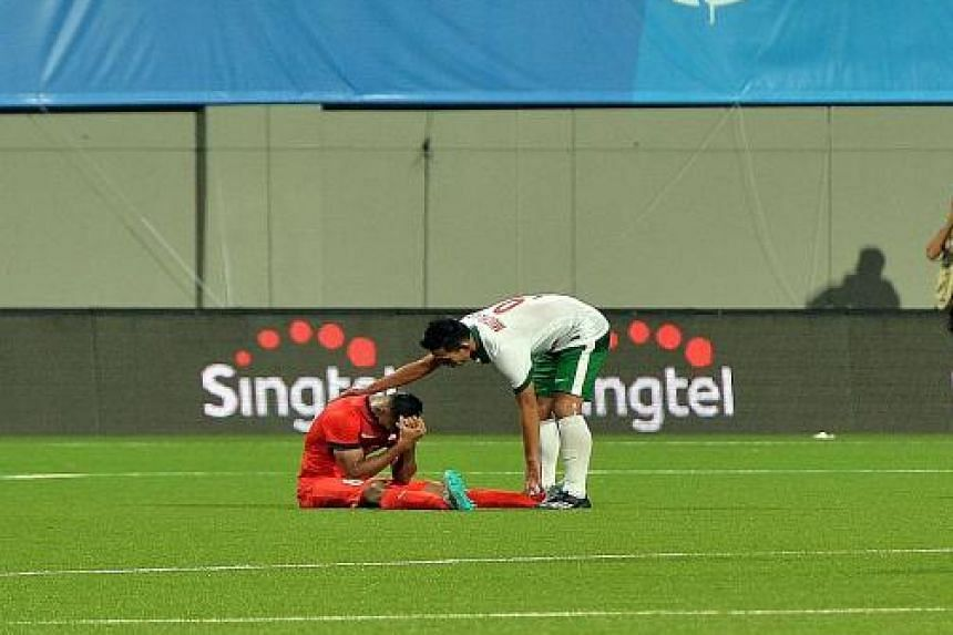 CHIVALRY: Footballer Muchlis Hadi Syaifulloh of Indonesia (in white) reaches out to console the distraught Anumanthan Mohan of Singapore after the hosts were beaten 1-0 and exited the tournament.