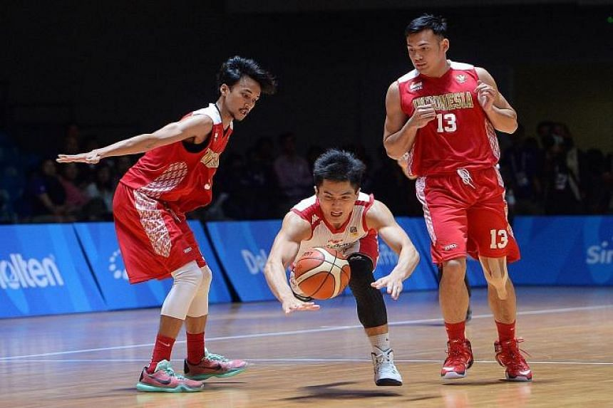 COURAGE: Singapore's Wong Wei Long (white, centre) hitting the deck under the challenge of his opponents during the basketball defeat by Indonesia, but still has his eyes firmly fixed on the ball.