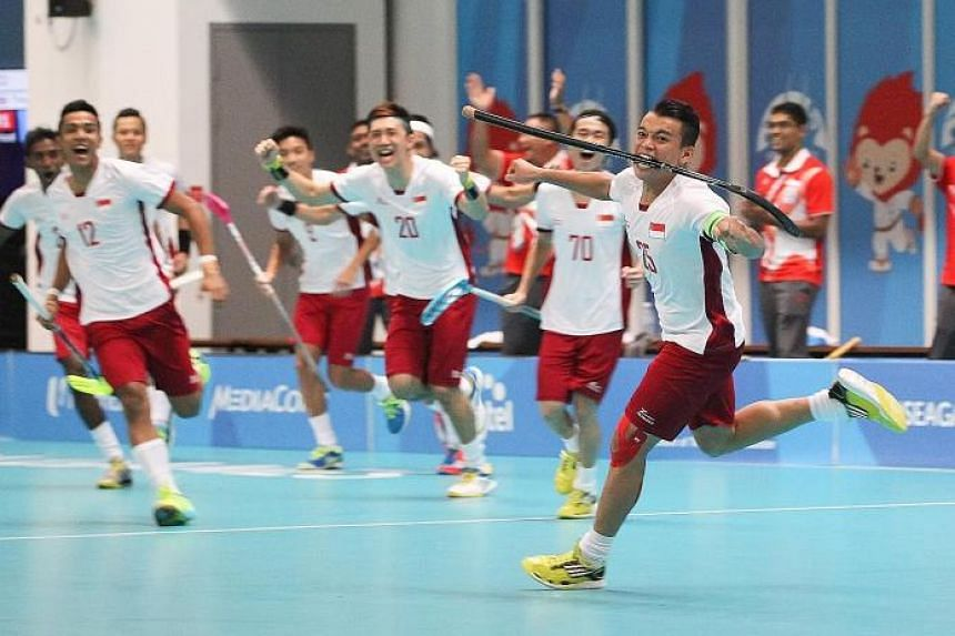 JOY: Singapore floorball player Ramlee Syazni (right) celebrates wildly with his team-mates after scoring a goal against Thailand at ITE College Central.