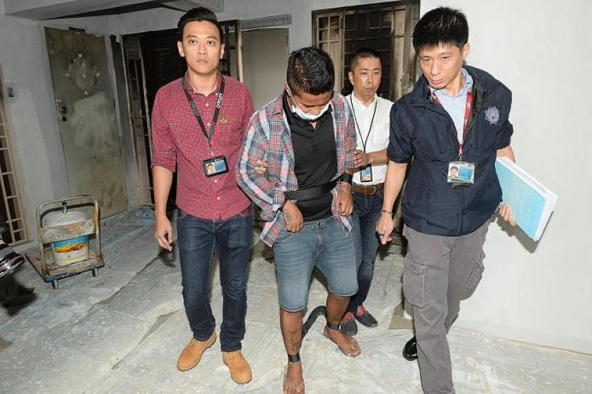Police and the suspected arsonist at the scene of his alleged crime in Toh Guan Road yesterday. The man is said to have been involved in setting fire to two flats located above a client of a loanshark.