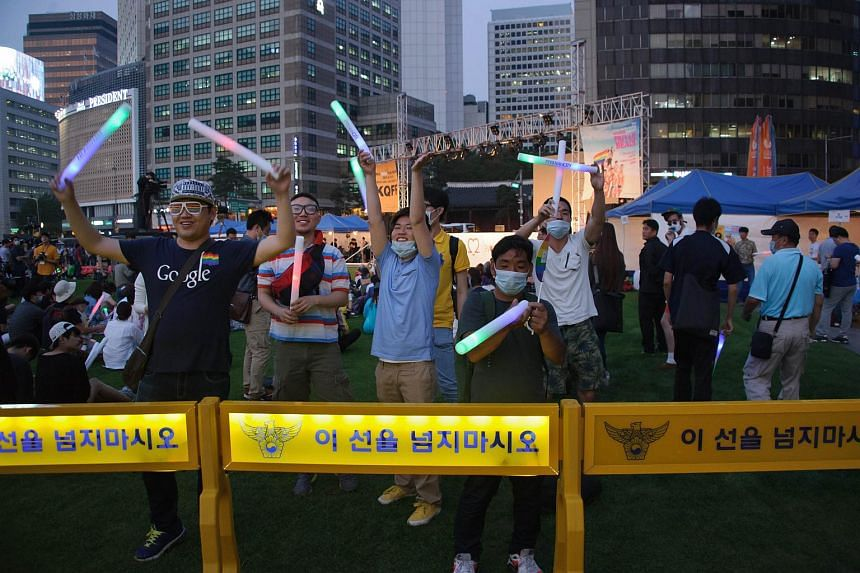 Members of the LGBT community gesture to conservative Christian anti-gay rights activists during the opening ceremony of the Queer Korea gay pride festival in Seoul.