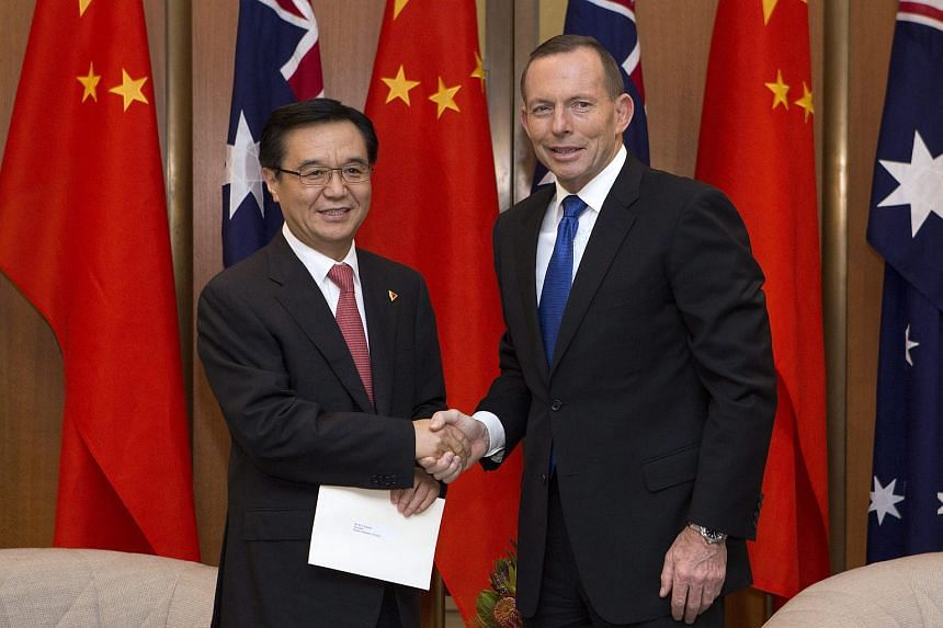 Australian Prime Minister Tony Abbott (right) shakes hands with China's Minister of Commerce Gao Hucheng at Parliament House in Canberra, Australia.