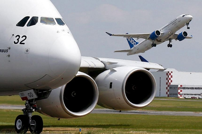 A Bombardier CS300 aircraft takes off as an Airbus A380 waits on the taxiway during the 51st Paris Air Show.