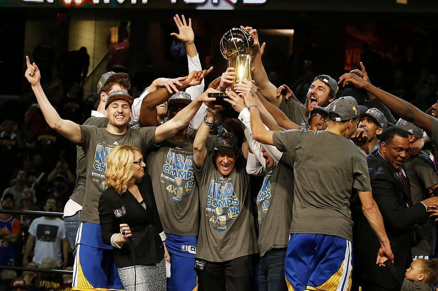 The Golden State Warriors celebrates with the Larry O'Brien NBA Championship Trophy after winning Game Six of the 2015 NBA Finals against the Cleveland Cavaliers.