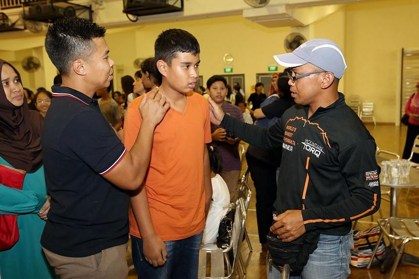Mountain Torq trainer Hajiris Sulomin (right) speaking with Tanjong Katong Primary School pupil Emyr Uzayr (centre) and his father Sadri Farick at the school on Wednesday, June 17, 2015.