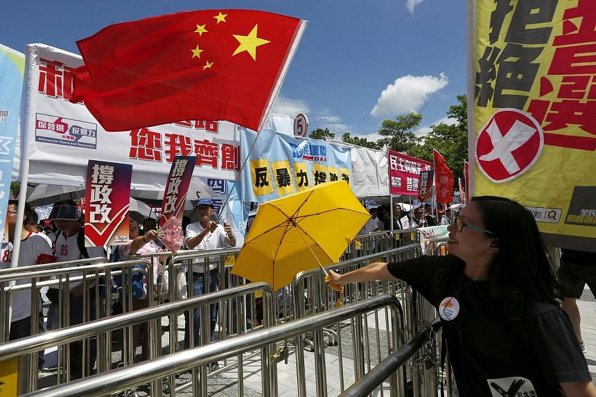 A pro-democracy protester carrying a yellow umbrella, symbol of the Occupy Central movement, demonstrates in front of pro-China supporters.