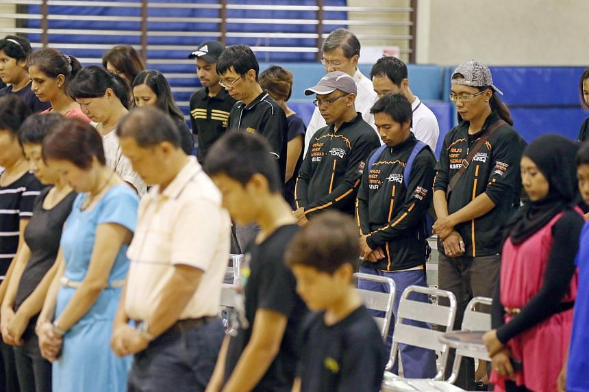 Mountain Torq trainers from Sabah (from right) Hillary Augustinus, James Maikol  and Hajiris Sulomin (grey/white cap), observing a minute of silence with Tanjong Katong Primary School students, teachers and their families, before meeting them in pers