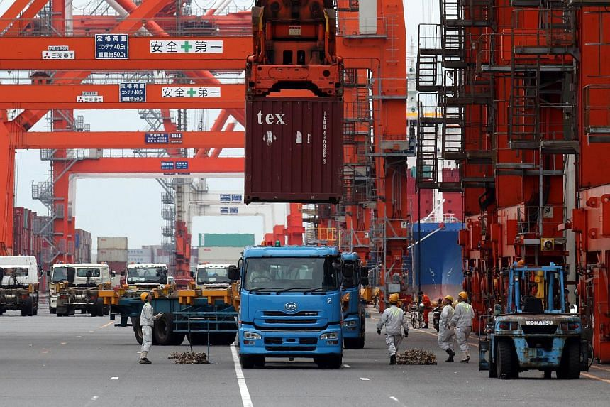 A container is loaded onto a flatbed truck from an international freighter at the international cargo terminal at Tokyo's port.