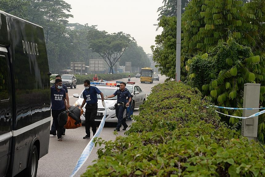 Police removing the body found in the vegetation by the Bukit Timah Expressway yesterday.