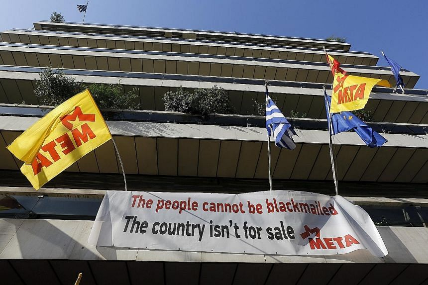 A banner hung up at the EU offices in Athens during a protest. Unless Greece settles its differences with the rest of Europe, it will run out of money to make a $2.4 billion debt repayment to the IMF at the end of this month.