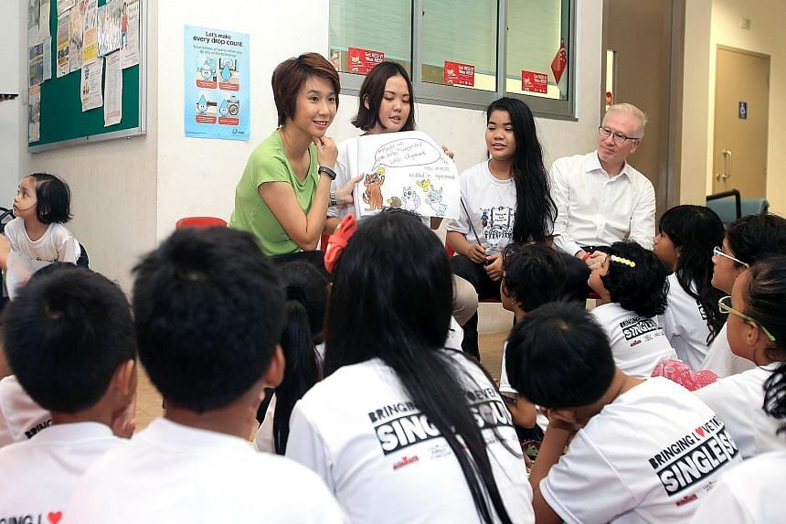 Bless founder Francesca Wah (second from left) reading stories to some of the children in the scheme. She is joined by (from left) Mayor of South West District Low Yen Ling, NUS student volunteer Nurul Khairiah Suhaimi and adviser to Clementi Grassro