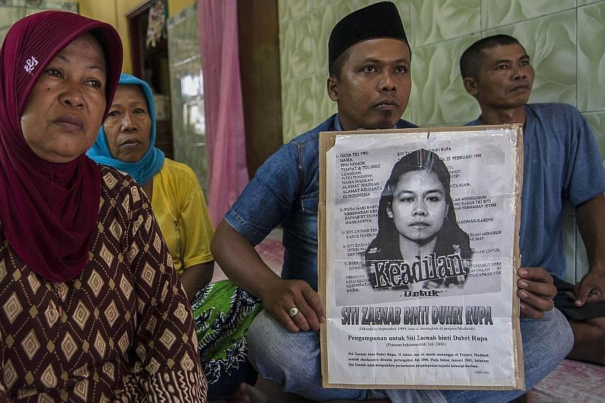 Family members of Indonesian maid Siti Zainab displaying a poster bearing her portrait. Siti was beheaded in April after being convicted of murder. President Joko Widodo announced last month that Indonesia would stop sending domestic workers to 21 Mi