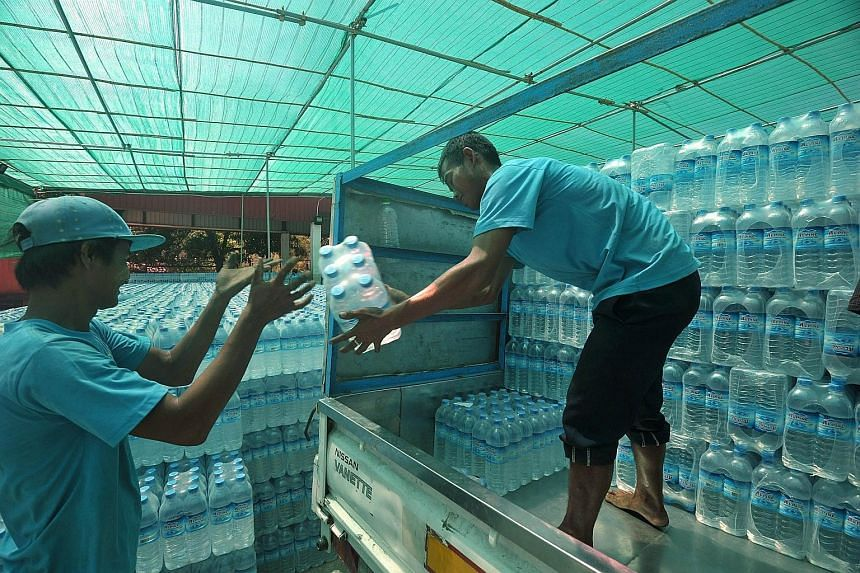 Workers loading bottles of water onto a truck at a distribution centre in Yangon. Bottled water is among the plethora of consumer industries set to take off as the country emerges from decades of isolated junta rule.