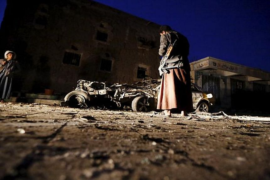 An armed man looks at the wreckage of a car at the site of a car bomb attack in Yemen's capital Sanaa.