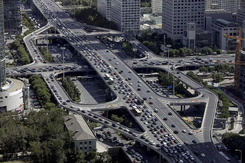 Vehicles drive on the Guomao Bridge through Beijing's central business district on June 11, 2015. China will step up investment in key sectors, including urban transport and shantytown renovation.