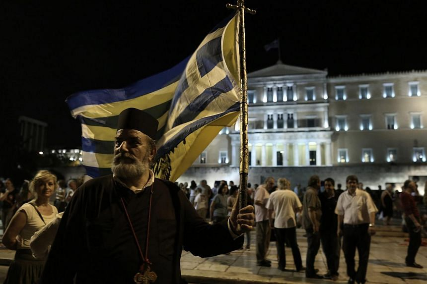 A Greek orthodox priest holds a Greek flag as he takes part in a rally against austerity, supporting the government on the negotiations with its international creditors.