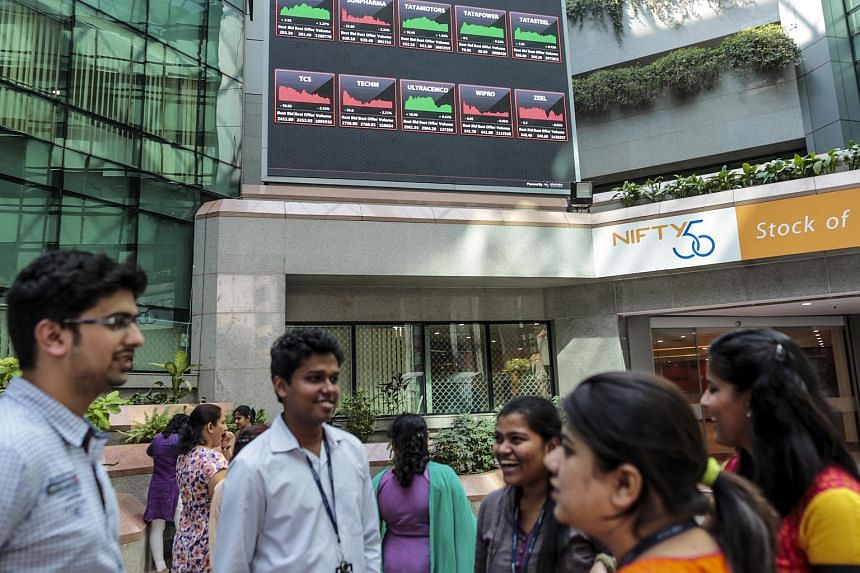 Employees standing front of an electronic board indicating the latest stock figures at the National Stock Exchange (NSE) in Mumbai, India.