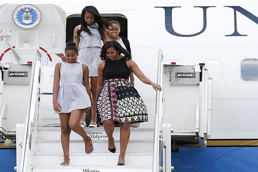 Michelle Obama arrives with her daughters Sasha (left) and Malia (top) in Milan, Italy.