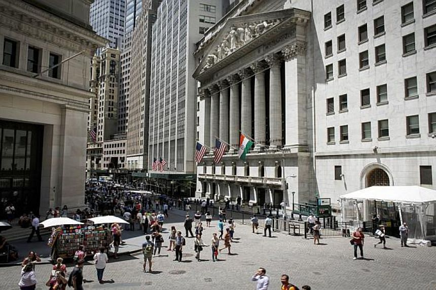 People walk by the New York Stock Exchange in New York on June 17, 2015.