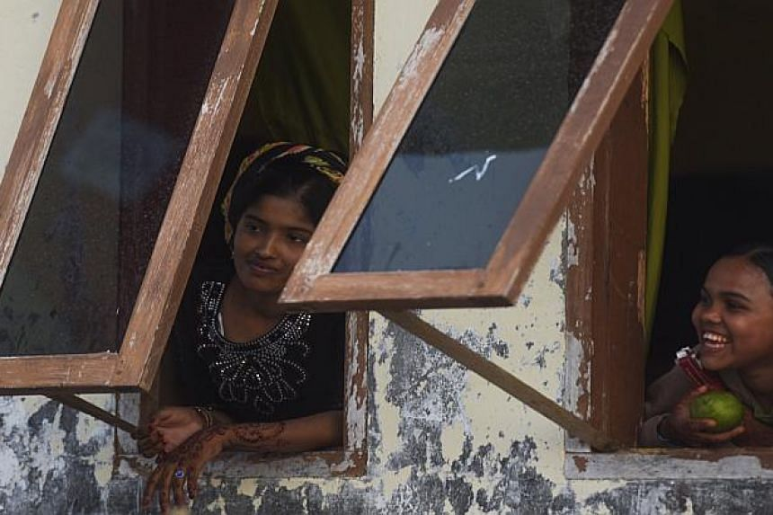 Rohingya migrants look out of windows at a temporary shelter in Aceh province, Indonesia on June 1, 2015.
