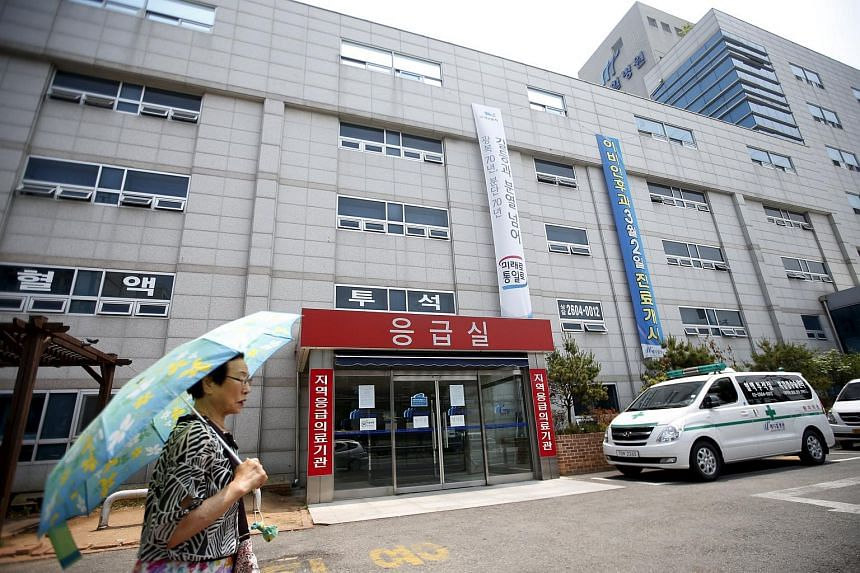 A woman holding an umbrella walks past a hospital which is sealed off temporarily, in Seoul, South Korea, on June 16, 2015.