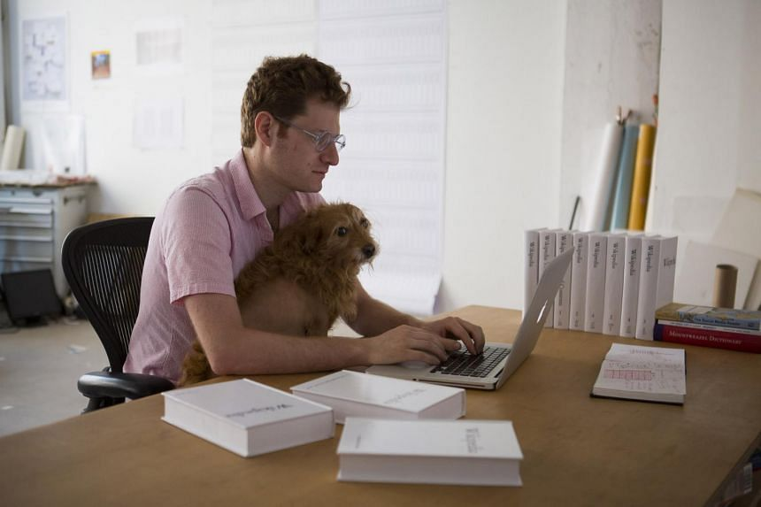 Michael Mandiberg (left) with his dog, Freddie Merckx, working on his Print Wikipedia project, which, will print some of the text from the reference website into physical books.