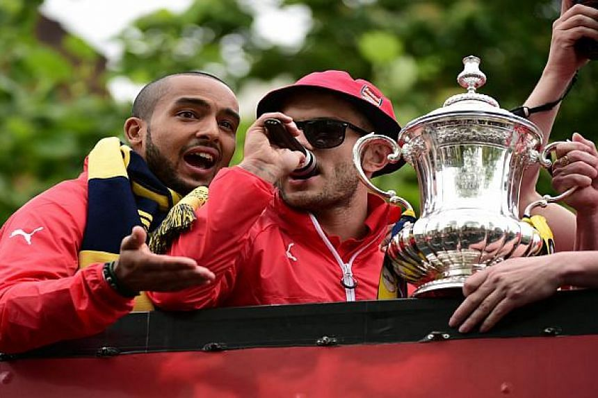 Arsenal midfielders Jack Wilshere (right) and Theo Walcott aboard the open-top bus in May.