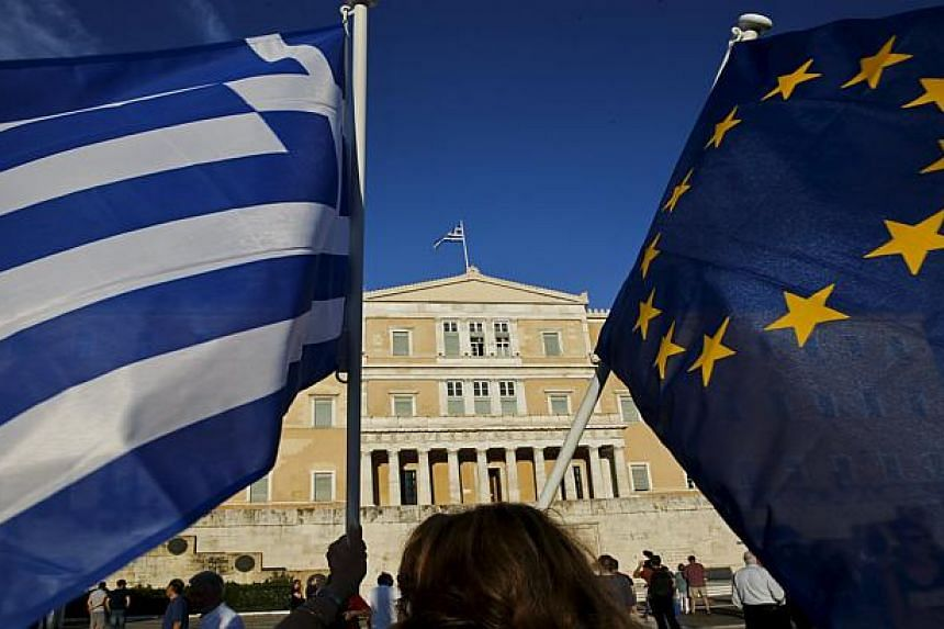 A woman waves a Greek national flag (left) and a European Union flag during a rally in Athens on June 18, 2015.